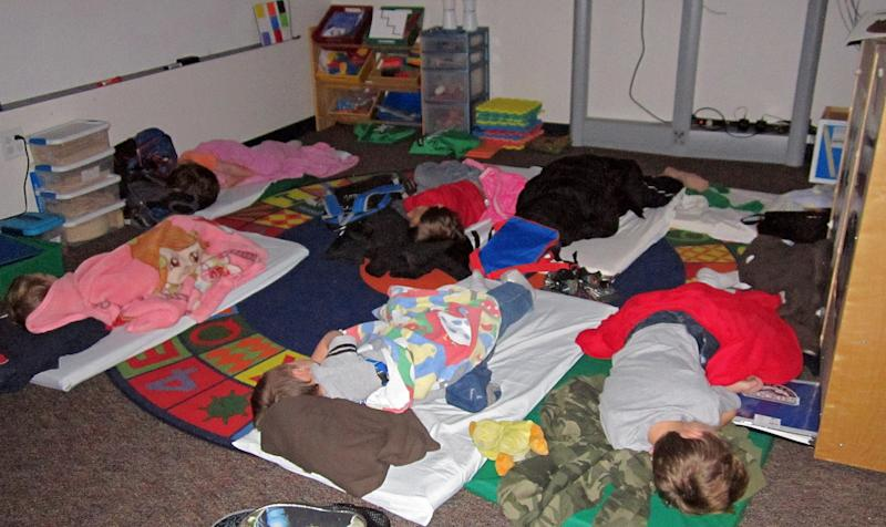 In this photo provided by Sharon Webb, principal of Miami-Yoder School, students sleep on the floor at the school on Wednesday, Feb. 25, 2013, in Yoder, Colo.  About 60 students were forced to spend the night at the school after snow drifts closed roads in the area. The students went home later Wednesday after the roads were cleared. (AP Photo/Sharon Webb)