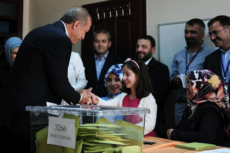 Turkish President Recep Tayyip Erdogan (L) shakes hands with a girl after voting in Turkey's general election at a polling station in Istanbul on June 7, 2015 (AFP Photo/Ozan Kose)
