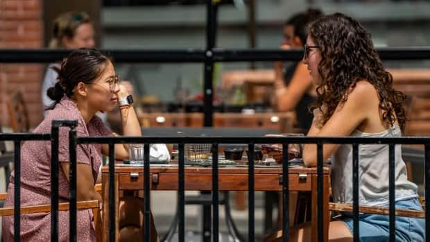 People have lunch together on a patio Friday, the day outdoor dining and non-essential retail returned in Ottawa. (Mathieu Theriault/CBC - image credit)