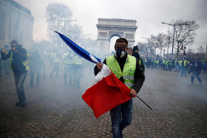 """A protester wearing a yellow vest holds a French flag as he walks among tear gas on the Champs-Elysees Avenue near the Arc de Triomphe during a national day of protest by the """"yellow vests"""" movement in Paris, France, Dec. 8, 2018. (Photo: Christian Hartmann/Reuters)"""