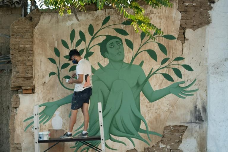 """Greek artist Fikos works on his latest mural titled """"Amaracus"""" in the Cypriot capital Nicosia"""