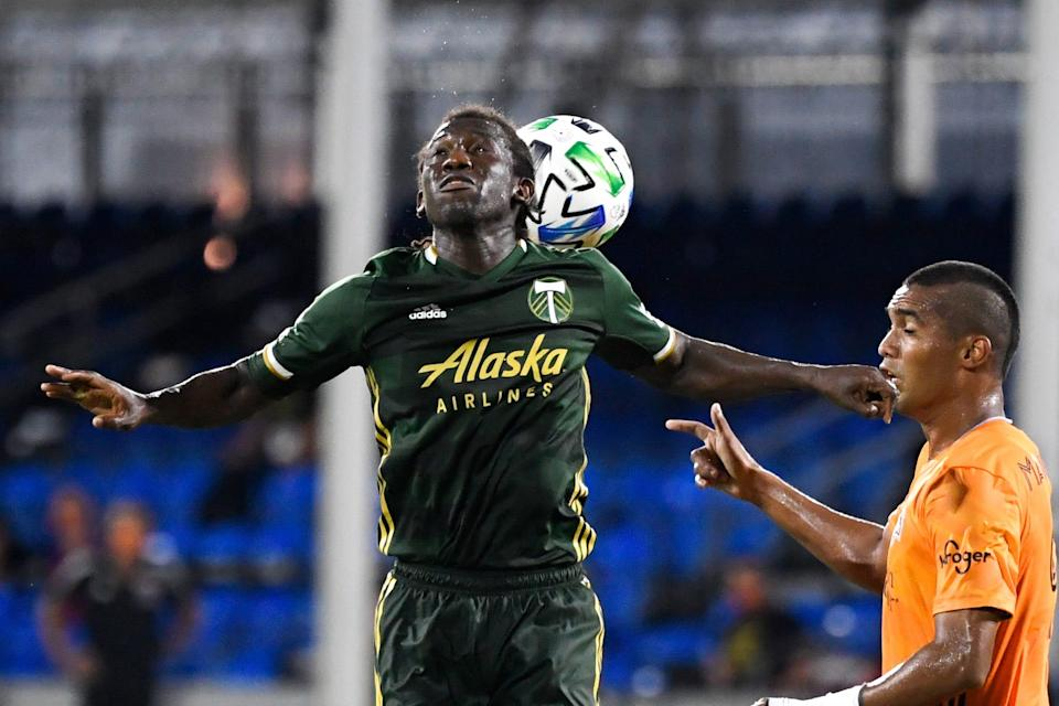 The Portland Timbers' Diego Chara and Houston Dynamo's Mauro Manotas fight for a header during the MLS is Back Tournament at ESPN Wide World of Sports on July 18. Portland won the game, 2-1.