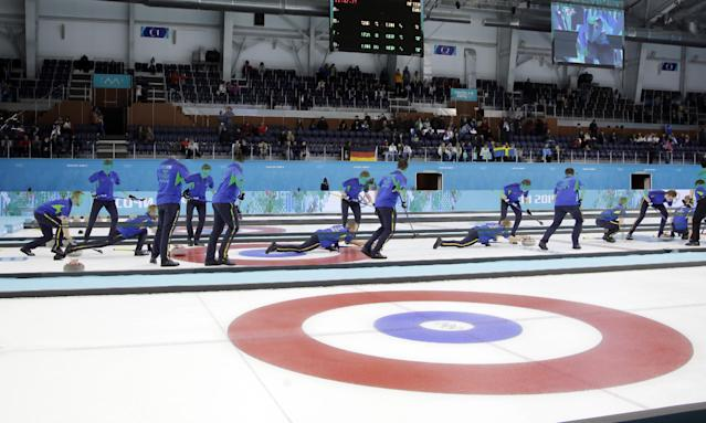 This multiple exposure photo shows the Sweden curling team throwing during a round robin session against China in the Ice Cube Curling Center at the 2014 Winter Olympics, Friday, Feb. 14, 2014, in Sochi, Russia. (AP Photo/Morry Gash)