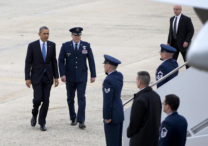 President Barack Obama prepares to board Air Force One at Andrews Air Force Base, Md., Wednesday, April 2, 2014, en route to the University of Michigan to speak about his proposal to raise the national minimum wage. (AP Photo/Carolyn Kaster)