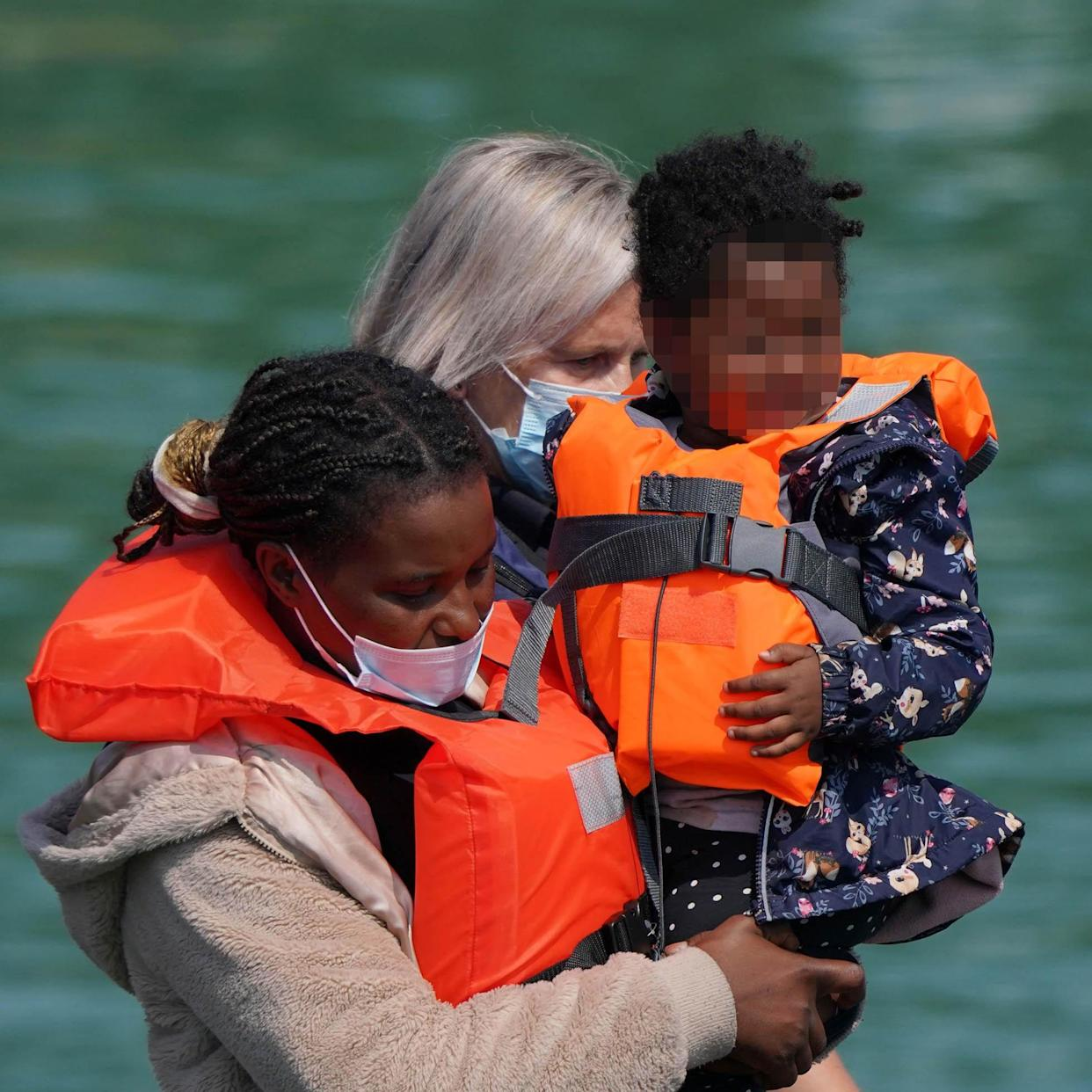 A group of people thought to be migrants are brought in to Dover, Kent, by Border Force officers following a small boat incident in the Channel (Gareth Fuller/PA)