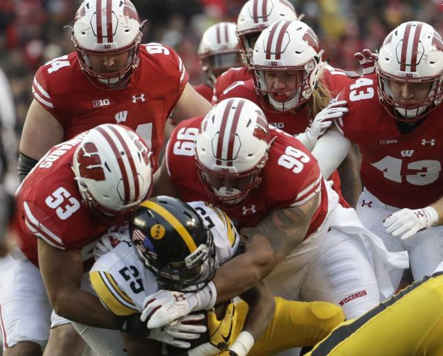 Iowa's Akrum Wadley is stopped during the first half of an NCAA college football game against Wisconsin Saturday, Nov. 11, 2017, in Madison, Wis. (AP Photo/Morry Gash)