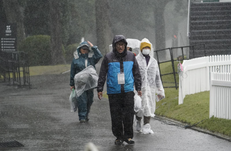 Volunteers walk in the rain after the second round of the Zozo Championship PGA Tour is postponed due to heavy rain at the Accordia Golf Narashino country club in Inzai, east of Tokyo, Japan, Friday, Oct. 25, 2019. (AP Photo/Lee Jin-man)