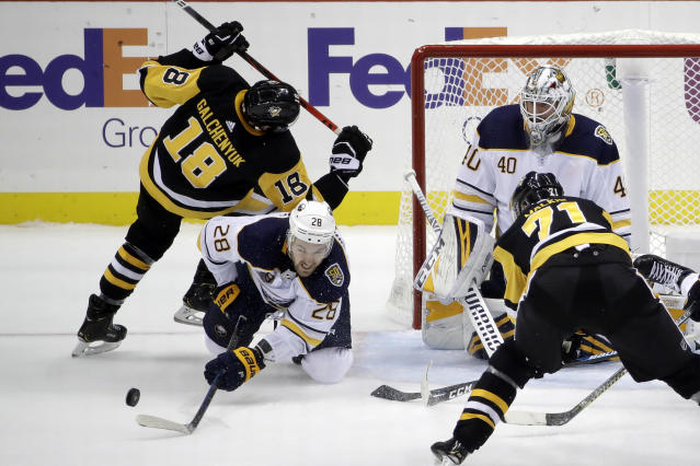 Buffalo Sabres' Zemgus Girgensons (28) clears the puck in front of goaltender Carter Hutton (40) while Pittsburgh Penguins' Alex Galchenyuk (18) and Evgeni Malkin (71) look for a shot near the end of an NHL hockey game in Pittsburgh, Thursday, Oct. 3, 2019. The Sabres won 3-1. (AP Photo/Gene J. Puskar)