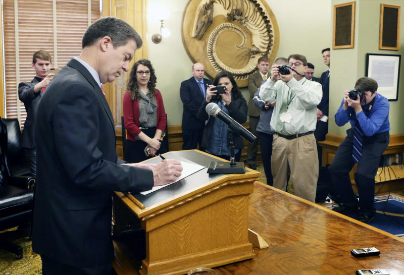 After announcing he would veto the tax bill sent to him by the legislature, Gov. Sam Brownback officially signs the veto, in his ceremonial office Wednesday, Feb. 22, 2017, as he stood in front of the assembled media. (Thad Allton /The Topeka Capital-Journal via AP)