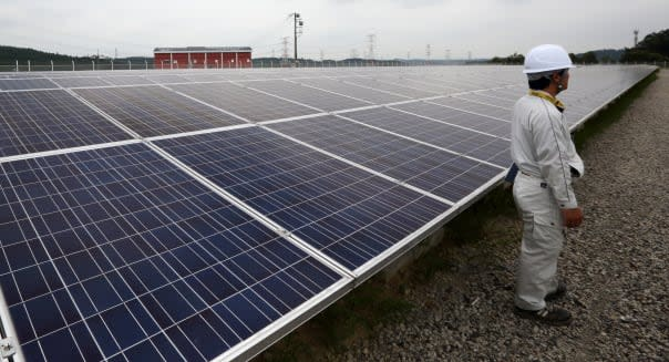 A worker stands near solar panels, manufactured by Sharp Corp., at the SoftBank Yaita Solar Park operated by SB Energy Corp. in Yaita City, Tochigi Prefecture, Japan, on Tuesday, Aug. 20, 2013. The 3 megawatt solar power station is scheduled to start operations from Aug. 23. Photographer: Tomohiro Ohsumi/Bloomberg via Getty Images