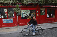 A cyclist passes a closed bar in the Temple bar area of Dublin, Ireland, Wednesday, Oct. 21, 2020. With COVID-19 cases on the rise, the government has imposed a tough new lockdown, shutting down non-essential shops, limiting restaurants to takeout service and ordering people to stay within five kilometers (three miles) of their homes for the next six weeks. (AP Photo/Peter Morrison)