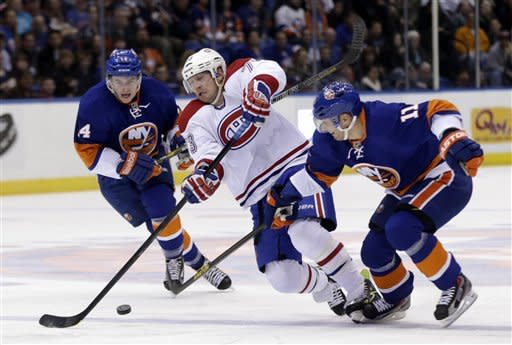 Montreal Canadiens' Michael Ryder, center, tries to skate through New York Islanders' Lubomir Visnovsky, right, and Brad Boyes during the first period of an NHL hockey game Thursday, March 21, 2013, in Uniondale, N.Y. (AP Photo/Seth Wenig)