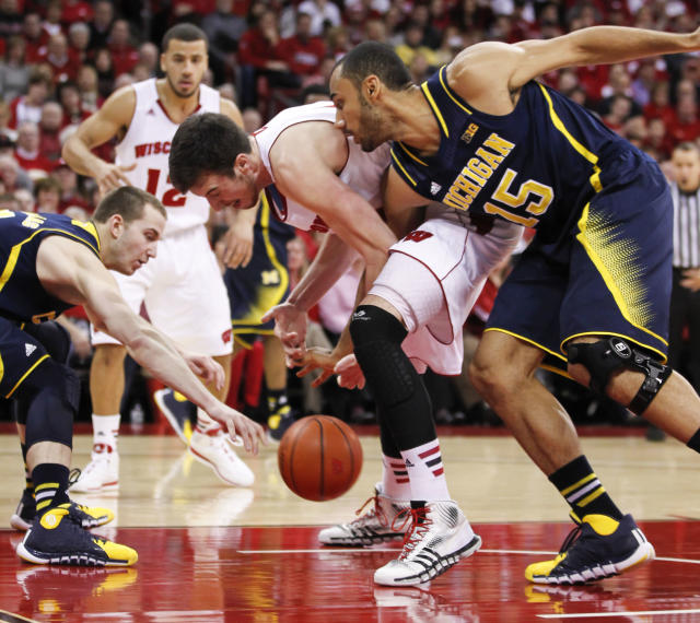 Michigan's Nik Stauskas, left, and Jon Horford (15) and Wisconsin's Frank Kaminsky reach for a loose ball during the first half of an NCAA college basketball game Saturday, Jan. 18, 2014, in Madison, Wis. (AP Photo/Andy Manis)