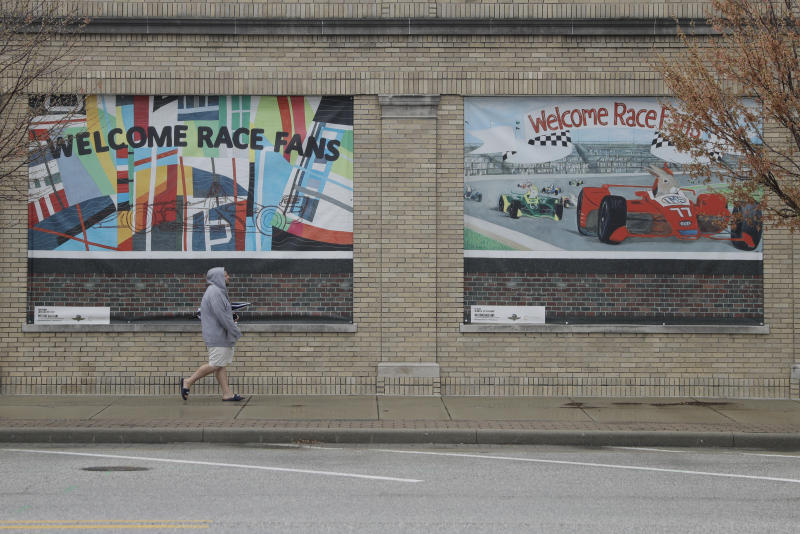 A man walks past signs for the Indianapolis 500, Wednesday, April 15, 2020, in Indianapolis. Indianapolis Motor Speedway, home of the Indianapolis 500, is closed due to the coronavirus pandemic. (AP Photo/Darron Cummings)