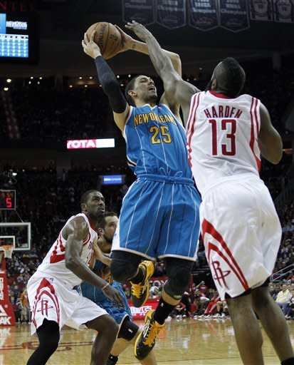 New Orleans Hornets shooting guard Austin Rivers (25) is fouled by Houston Rockets shooting guard James Harden (13) and power forward Patrick Patterson (54) while driving to the basket during the first half of an NBA basketball game on Wednesday, Jan. 2, 2013, in Houston. (AP Photo/Bob Levey)
