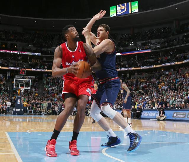Los Angeles Clippers center DeAndre Jordan, left, drives the lane for shot as Denver Nuggets center Timofey Mozgov, of Russia, covers in the first quarter of an NBA basketball game in Denver on Monday, March 17, 2014. (AP Photo/David Zalubowski)