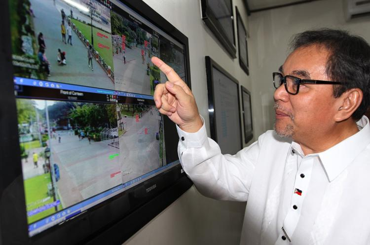 Tourism Secretary Ramon Jimenez Jr. inspects the closed-circuit television (CCTV) camera monitor installed at the command center of the National Parks Development Committee (NPDC) in Manila, Nov. 27, 2012. The project is part of efforts to protect tourists and visitors at the park from criminal elements. (Paulo Vecina, NPPA Images)