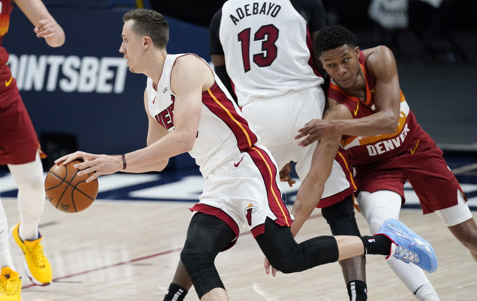 Miami Heat guard Duncan Robinson, left, drives past Denver Nuggets guard PJ Dozier during the first half of an NBA basketball game Wednesday, April 14, 2021, in Denver. (AP Photo/David Zalubowski)