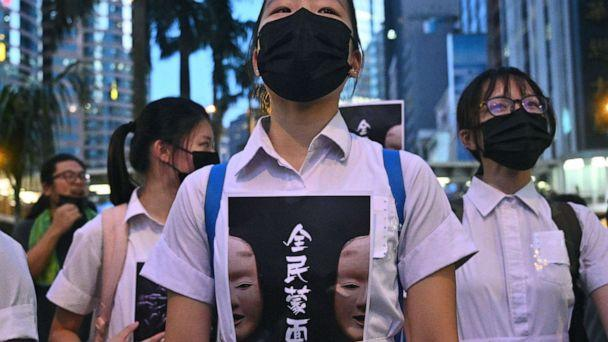 PHOTO: TOPSHOT - High school students chant slogans as they stick posters reading 'all people masked' on their uniforms as protesters gather in Hong Kong, Oct. 4, 2019, after the government announced a ban on face masks. (Philip Fong/AFP via Getty Images)