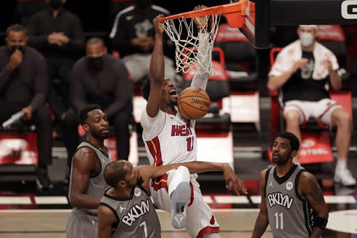 Miami Heat center Bam Adebayo dunks over Brooklyn Nets forward Kevin Durant (7) and guard Kyrie Irving (11) during the first half of an NBA basketball game Monday, Jan. 25, 2021, in New York. (AP Photo/Adam Hunger)