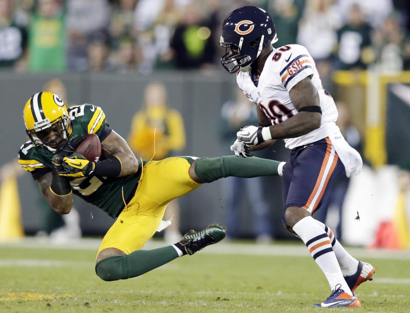 FILE - In this Sept. 13, 2012, file photom, Green Bay Packers' Charles Woodson intercepts a pass in front of Chicago Bears' Earl Bennett (80) during the second half of an NFL football game in Green Bay, Wis. Woodson signed a one-year contract with the Oakland Raiders on Tuesday, may 21, 2013, to return to his original team after leaving seven years ago for Green Bay as a free agent. The  36-year-old was released by the Packers in a salary-cutting move Feb. 15, with two years remaining on his contract. (AP Photo/Morry Gash, File)