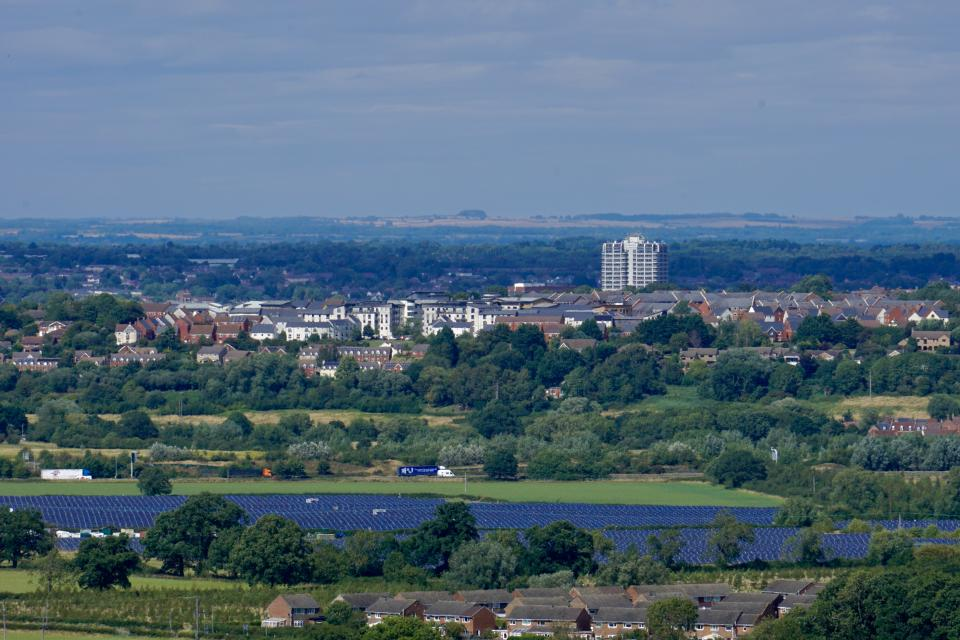 A view of Swindon showing Wroughton in foreground, solar farm, M4 motorway and the sprawling town of Swindon stretching to the horizon including the iconic DMJ Tower.
