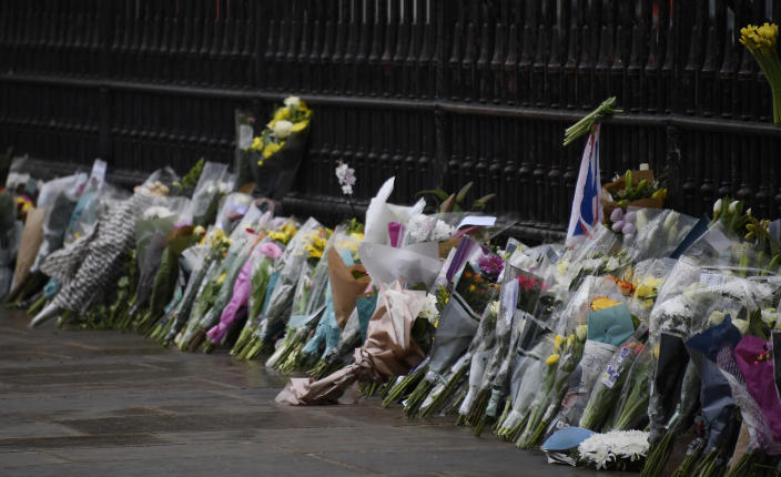 Flowers line the sidewalk in front of the gate outside Buckingham Palace in London, a day after the death of Britain's Prince Philip, Saturday, April 10, 2021. Britain's Prince Philip, the irascible and tough-minded husband of Queen Elizabeth II who spent more than seven decades supporting his wife in a role that mostly defined his life, died on Friday. (AP Photo/Alberto Pezzali)