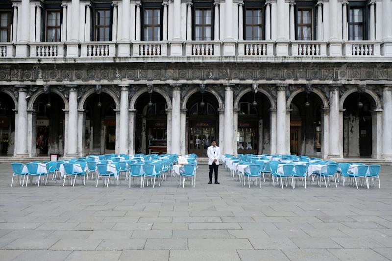 A waiter stands by empty tables outside a restaurant at St Mark's Square, which is usually full of tourists, after Italy's government adopted a decree with emergency new measures to contain the coronavirus, in Venice, Italy, March 5, 2020. Italy?s tourism industry has been suffering hugely since the outbreak. REUTERS/Manuel Silvestri (Photo: Manuel Silvestri / reuters)