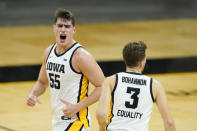 Iowa center Luka Garza (55) celebrates with teammate Jordan Bohannon (3) after making a 3-point basket during the first half of an NCAA college basketball game against Minnesota, Sunday, Jan. 10, 2021, in Iowa City, Iowa. (AP Photo/Charlie Neibergall)