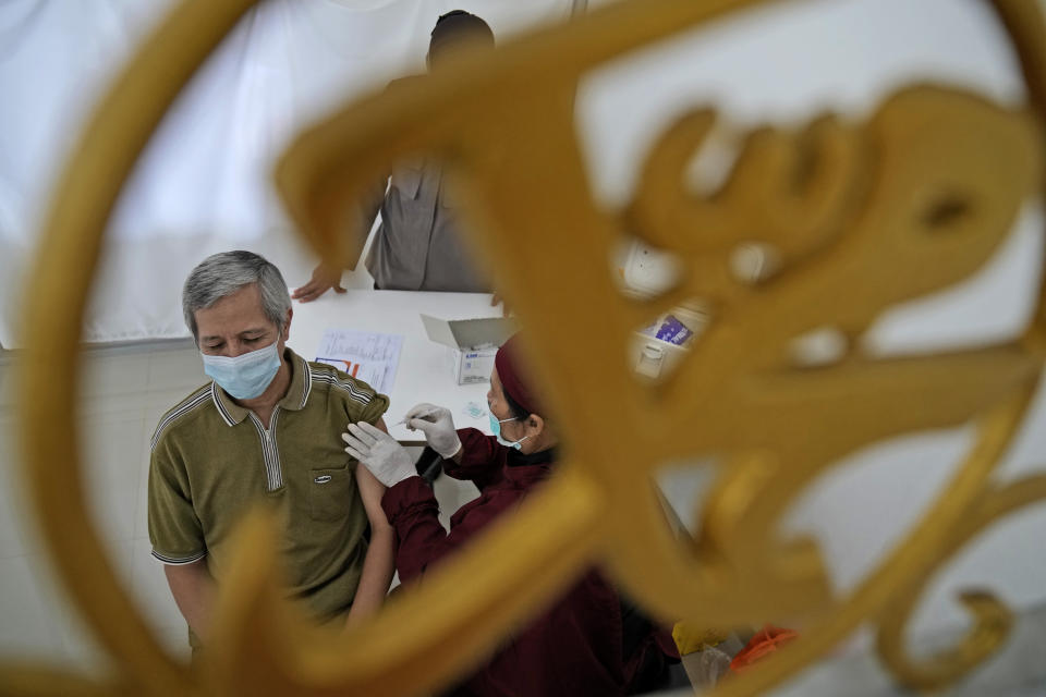 """A man is seen through a mosque ornament in Arabic writing that reads: """"Muhammad"""" as he receives a shot of the AstraZeneca vaccine for COVID-19 during a mass vaccination in Depok on the outskirts of Jakarta, Indonesia, Saturday, June 19, 2021. Indonesia, the world's fourth most populous country, aims to inoculate more than 181 million of its 270 million people by March 2022 but progress have been slow due to limited global vaccine supply, the unpreparedness of the national health system and vaccine hesitancy. (AP Photo/Dita Alangkara)"""