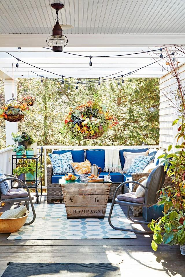 <p>Any porch can look fall-ready with the right decorating treatment. Though the cushions and carpet here are a nice coastal cobalt blue, the hanging plants and orange foliage give it a cozier, autumn atmosphere. The string lights also make it feel more intimate. </p>