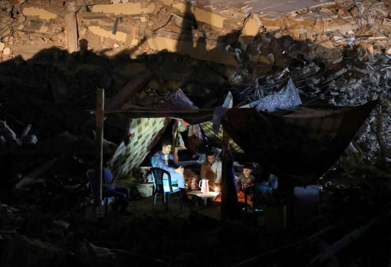 Palestinians camp out in the ruins of a building in Gaza destroyed in an air strike during Israel's 11-day bombardment of the densely populated territory