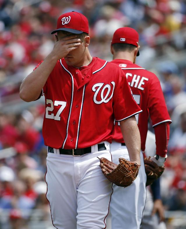 Washington Nationals starting pitcher Jordan Zimmermann wipes his brow during the third inning of a baseball game against the St. Louis Cardinals at Nationals Park on Saturday, April 19, 2014, in Washington. (AP Photo/Alex Brandon)