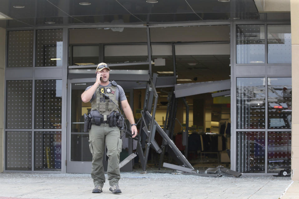 FILE - In this Sept. 20, 2019 file photo, a state police officer stands outside a damaged entrance to the Woodfield Mall after a man drove an SUV into a Sears store in the Chicago suburb of Schaumburg, Ill. On Friday, May 29, 2020, The Associated Press reported on stories circulating online incorrectly asserting that protesters looted the Mall of America in Bloomington, Minn., on Wednesday night, with a video showing someone driving a car through North America's largest shopping complex. No incidents occurred Wednesday or Thursday at the Mall of America, spokeswoman Sarah Grap confirmed to The Associated Press. The video was taken in September 2019 at the Woodfield Mall in Schaumburg, Ill. (John J. Kim/Chicago Tribune via AP)