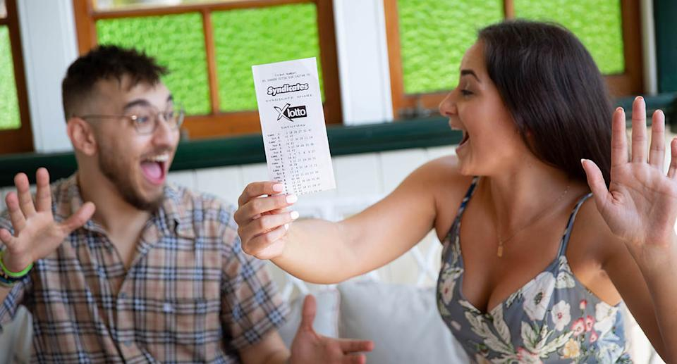 Two people excitedly hold up X Lotto ticket.