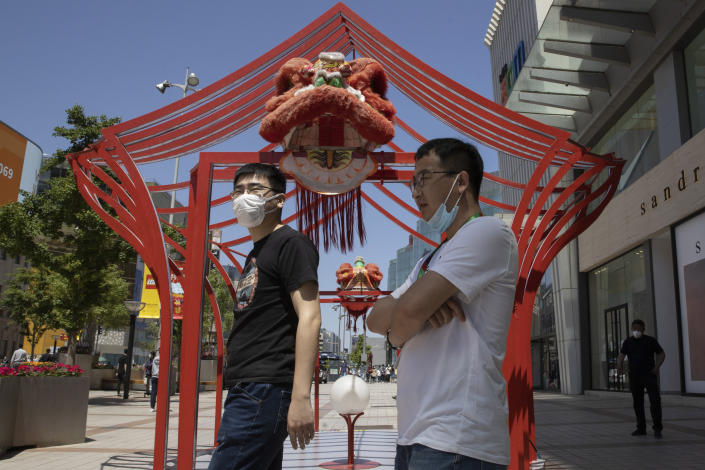 Residents wear masks against the coronavirus as they visit a retail district in Beijing on Tuesday, May 12, 2020. Shares were mostly lower Tuesday in Asia as worries over fresh outbreaks of coronavirus cases overshadowed hopes over reopening economies. (AP Photo/Ng Han Guan)