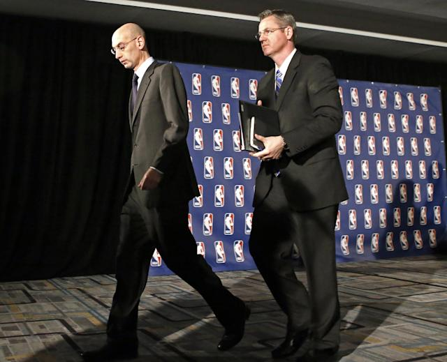 NBA Commissioner Adam Silver, left, walks away after a news conference in New York, Tuesday, April 29, 2014. Silver announced that Los Angeles Clippers owner Donald Sterling has been banned for life by the league in response to racist comments the league says he made in a recorded conversation. (AP Photo/Kathy Willens)
