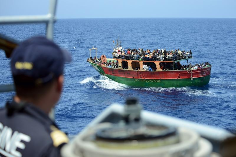 This handout picture taken by the French Navy on May 20, 2015 shows a crew member of the Commandant Birot patrol looking at migrants aboard a fishing boat during a rescue operation in the Mediterranean Sea (AFP Photo/)