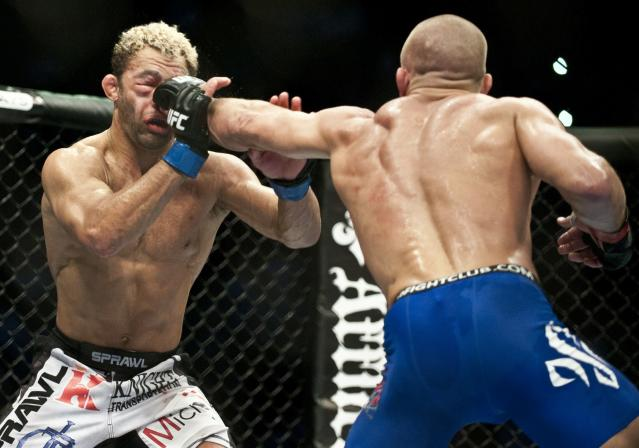 Georges St-Pierre (R) from Montreal, Canada punches in the face, Josh Koscheck from Waynesburg US on the fourth round of the Ultimate Fighting Championship on December 11, 2010 at Bell Centre in Montreal, Quebec, Canada. AFP PHOTO / ROGERIO BARBOSA (Photo credit should read ROGERIO BARBOSA/AFP/Getty Images)