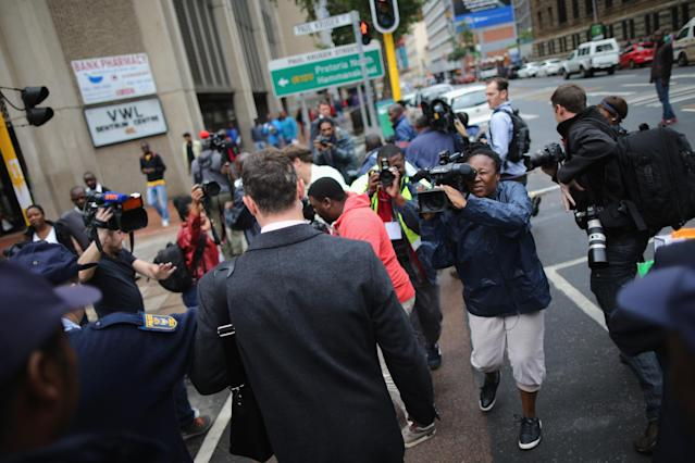 PRETORIA, SOUTH AFRICA - MARCH 05: Oscar Pistorius is pursued by media as he leaves North Gauteng High Court during a break on the third day of his trial accused of the murder of his girlfriend Reeva Steenkamp on March 5, 2014 in Pretoria, South Africa. Olympic and Paralympic athlete Oscar Pistorius, aged 27, is accused of murdering his girlfriend Reeva Steenkamp. Pistorius denies the allegation claiming he mistook Steenkamp for an intruder inside their home on Valentines Day 2013. (Photo by Christopher Furlong/Getty Images)