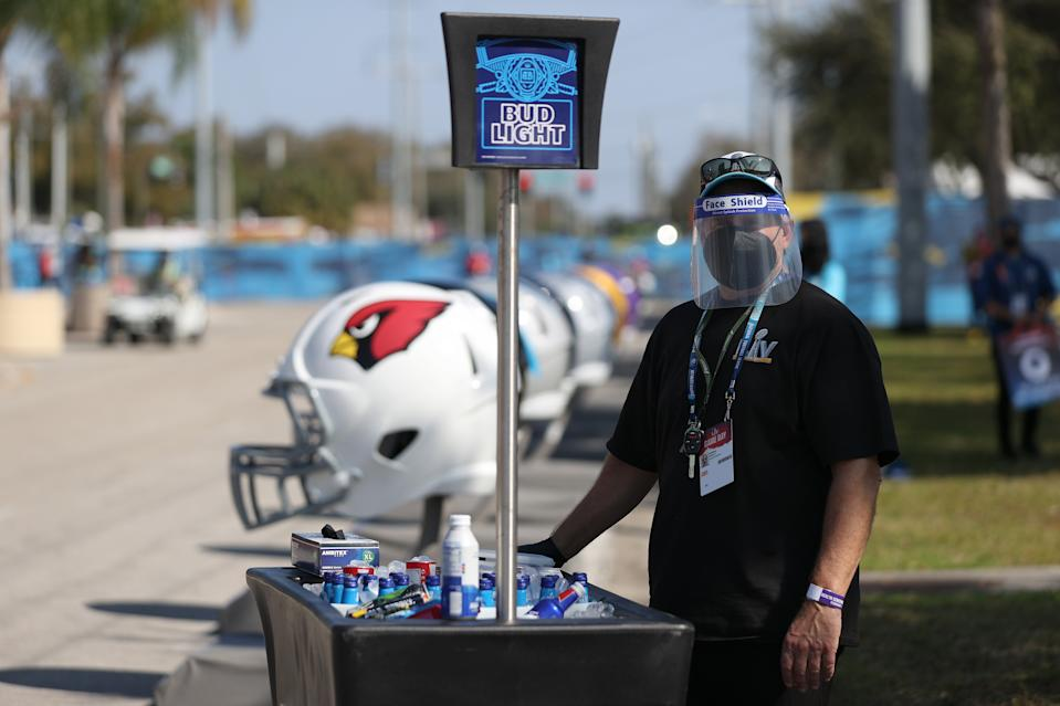 A vendor wears a mask while selling merchandise ahead of Super Bowl LV between the Tampa Bay Buccaneers and the Kansas City Chiefs at Raymond James Stadium on February 07, 2021 in Tampa, Florida. (Photo by Patrick Smith/Getty Images)