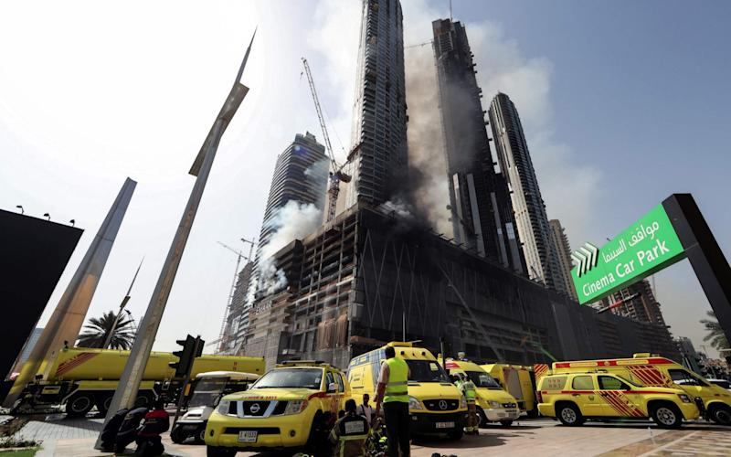 Members of the Dubai Civil Defence arrive at the scene of the fire which broke out on Sunday morning - AFP