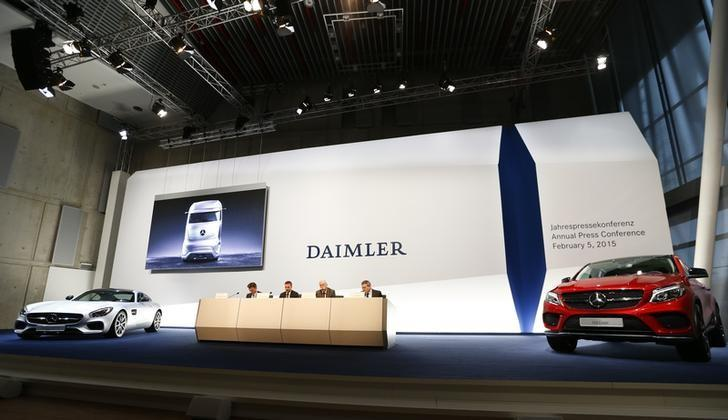 Daimler CEO Zetsche is flanked by two Mercedes sports cars at the annual news conference in Stuttgart