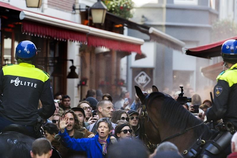 Protesters of the anti-Islam Pegida movement are contained by policemen on horseback in downtown Utrecht, on October 11, 2015 during a Pegida rally against the welcoming of refugees (AFP Photo/Jeroen Jumelet)