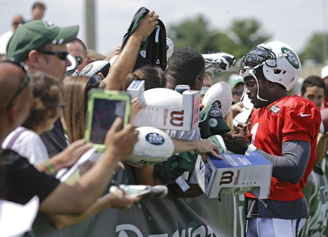 New York Jets quarterback Michael Vick (1) signs autographs for fans after practice during an NFL football training camp on Saturday, July 26, 2014, in Cortland, N.Y. (AP Photo/Frank Franklin II)