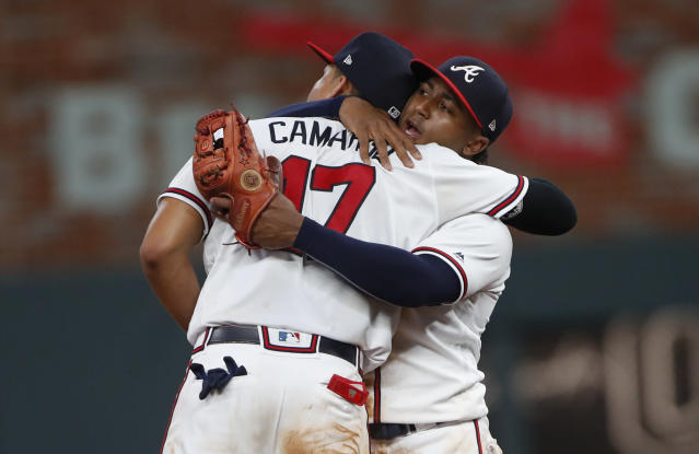 Atlanta Braves second baseman Ozzie Albies (1) and shortstop Johan Camargo (17) embrace after the Braves defeated the Chicago Cubs 4-1 in a baseball game Wednesday, May 16, 2018, in Atlanta. (AP Photo/John Bazemore)