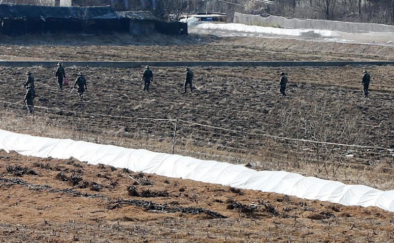 South Korean soldiers search for suspected North Korean leaflets on a field in the border city of Paju near the Demilitarized Zone dividing the two Koreas on January 13, 2016