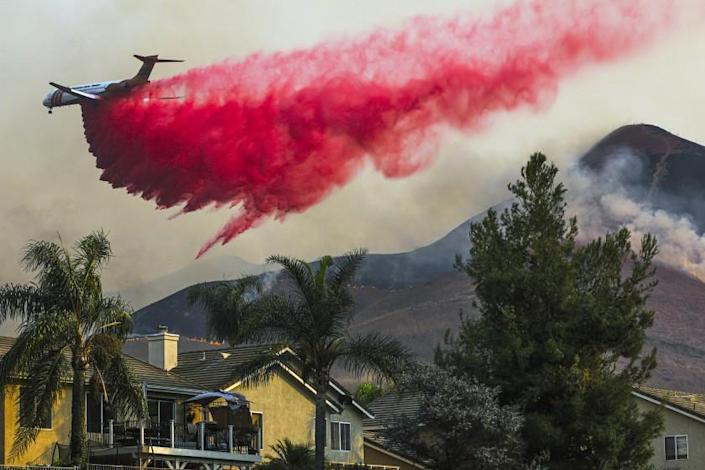 CHINO HILLS, CA - OCTOBER 27: Air tanker makes fire retardant drop behind homes on Tuesday, Oct. 27, 2020 in Chino Hills, CA. (Irfan Khan / Los Angeles Times)