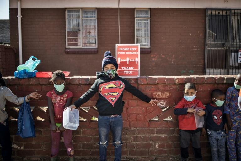 Children try to respect social distancing as they queue for food at the grassroots charity Hunger has no Religion in Johannesburg