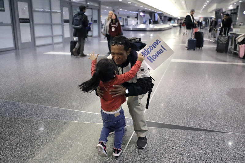 Thy Chea, of Lowell, Mass., center, originally of Cambodia, greets his daughter on his arrival at Boston's Logan Airport, Wednesday, Feb. 26, 2020, after getting his green card reinstated last year. Chea is the fourth Cambodian refugee to be allowed back into the country after being deported, and just the first on the East Coast, according to Asian American organizations that have been fighting increased deportations of Southeast Asians under President Donald Trump. (AP Photo/Steven Senne)